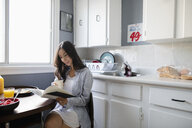 Young Latinx woman drinking coffee and reading book in morning kitchen - HEROF27969