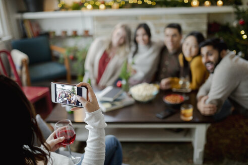 Woman with camera phone photographing friends in living room - HEROF28014