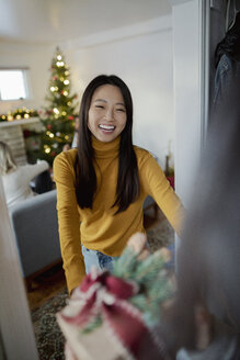 Happy young woman greeting friend with Christmas gift in doorway - HEROF28023