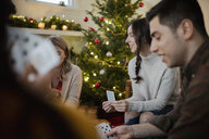 Friends playing cards in Christmas living room - HEROF28029