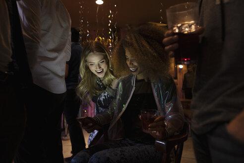 Young women friends using smart phone in dark nightclub - HEROF28050