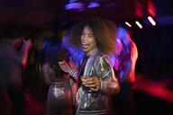 Portrait carefree young woman taking tequila shot in nightclub - HEROF28053