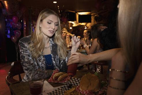 Women friends eating in nightclub - HEROF28077