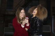 Laughing young women friends with smart phone on urban street - HEROF28086