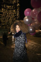 Portrait exuberant young woman with balloons on urban street at night - HEROF28104