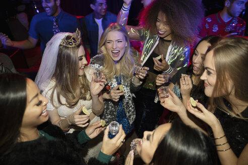 Bachelorette and friends taking tequila shots on dance floor in nightclub - HEROF28125