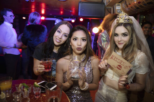 Portrait confident bachelorette and friends with kissing sign and jar in nightclub - HEROF28134