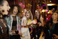 Confetti falling over laughing bachelorette and friends in nightclub - HEROF28137