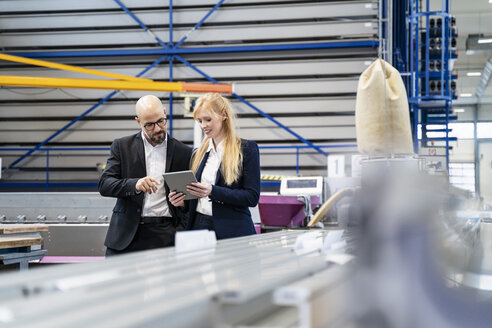 Businessman and businesswoman with tablet discussing in factory - DIGF06052