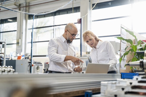 Businessman and businesswoman with laptop examining workpiece in factory - DIGF06058