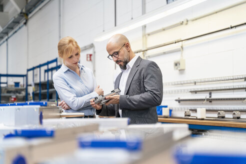 Businessman and businesswoman examining workpiece in factory - DIGF06121