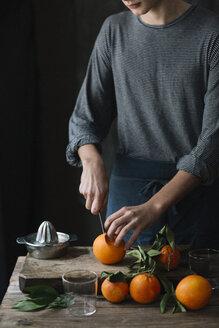 Young man cutting oranges - ALBF00773