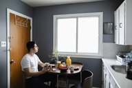 Thoughtful young Latinx man looking out window in morning kitchen - HEROF28155