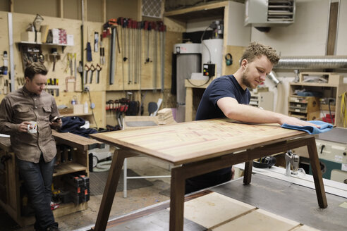 Male carpenter finishing coffee table in workshop - HEROF28260