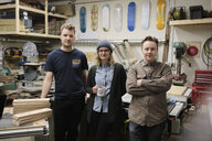 Portrait confident artists in workshop with recycled skateboards - HEROF28284
