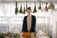 Portrait confident female artist drying flowers in studio - HEROF28323