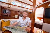 Young man in sailboat cabin with folding map, portrait - CUF49591