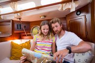 Young couple in sailboat cabin looking at folding map - CUF49594