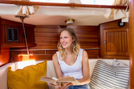 Young woman sitting in sailboat cabin with book - CUF49597