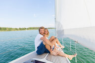 Young couple sailing on Chiemsee lake, portrait, Bavaria, Germany - CUF49609