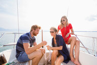 Young man and adult women tying rope knots on sailboat on Chiemsee lake, Bavaria, Germany - CUF49615