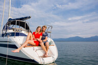 Young couple sitting on sailboat on Chiemsee lake, Bavaria, Germany - CUF49618