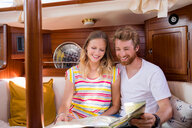 Young couple in sailboat cabin looking at folding map - CUF49627