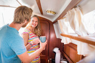 Young couple in sailboat cabin making coffee - CUF49630