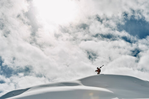 Male skier on top of snow covered mountain, Alpe-d'Huez, Rhone-Alpes, France - CUF49648