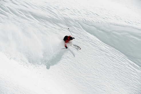 Male skier skiing down mountainside, high angle view, Alpe-d'Huez, Rhone-Alpes, France - CUF49678