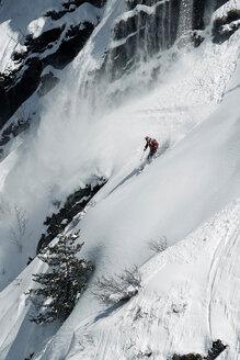 Male skier speeding down rugged vertical mountainside, Alpe-d'Huez, Rhone-Alpes, France - CUF49699