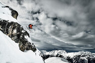 Male skier  jumping mid air from rugged mountainside, Alpe-d'Huez, Rhone-Alpes, France - CUF49702