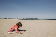 Side view of boy playing with sand at beach against sky during sunny day - CAVF63017