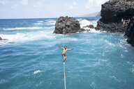Full length of carefree young man practicing slacklining over sea - CAVF63026