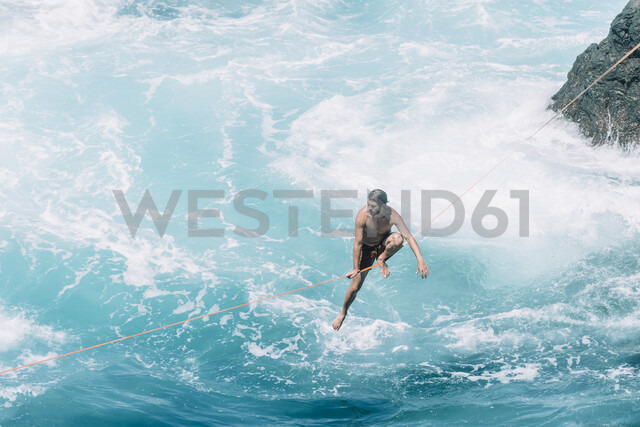 High angle view of carefree young man slacklining on rope over sea during sunny day - CAVF63029