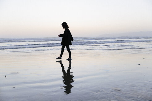 Side view of silhouette woman walking at beach against clear sky during sunset - CAVF63059