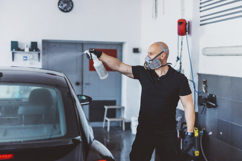 Worker cleaning car while standing in workshop - CAVF63065