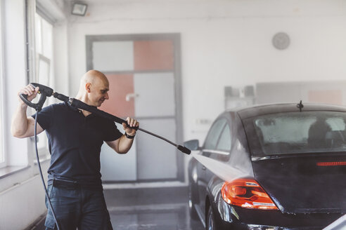 Male worker pouring water on car with hose in workshop - CAVF63074