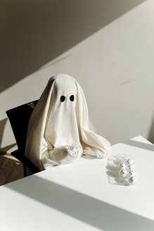 High angle view of man in ghost costume with egg carton on table sitting at home during Halloween - CAVF63098