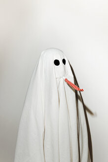 Man in ghost costume blowing party horn blower while standing against wall - CAVF63101