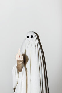 Man in ghost costume showing middle finger while standing against wall - CAVF63104