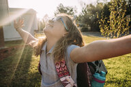 Happy girl with arms outstretched standing in yard during sunny day - CAVF63107