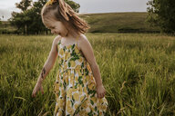 Happy cute girl looking down while standing on grassy field - CAVF63113