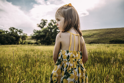 Rear view of cute girl looking away while standing on grassy field against cloudy sky - CAVF63116
