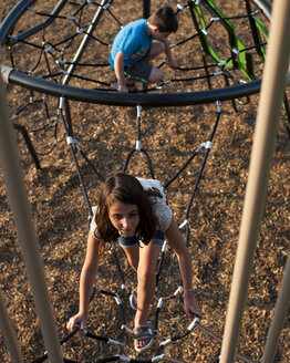 High angle view of siblings playing on jungle gym at playground - CAVF63131
