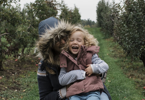 Happy mother with daughter sitting on grassy field in forest - CAVF63140