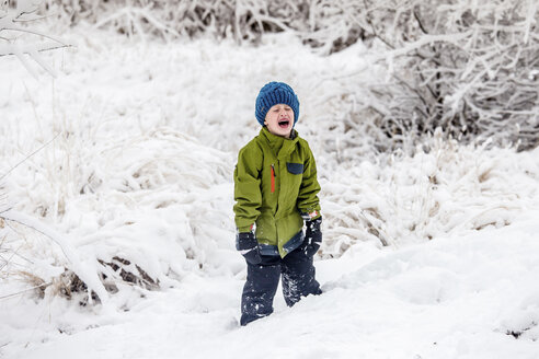 Boy crying while standing on snow covered field - CAVF63149