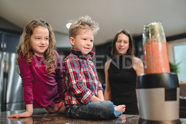 Mother and children watching blender making smoothie - ISF21010