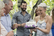 Woman serving anniversary cake to parents garden party - HEROF28399
