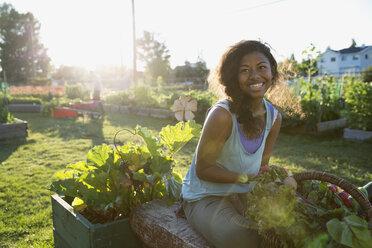 Smiling young woman harvesting vegetables in garden - HEROF28417
